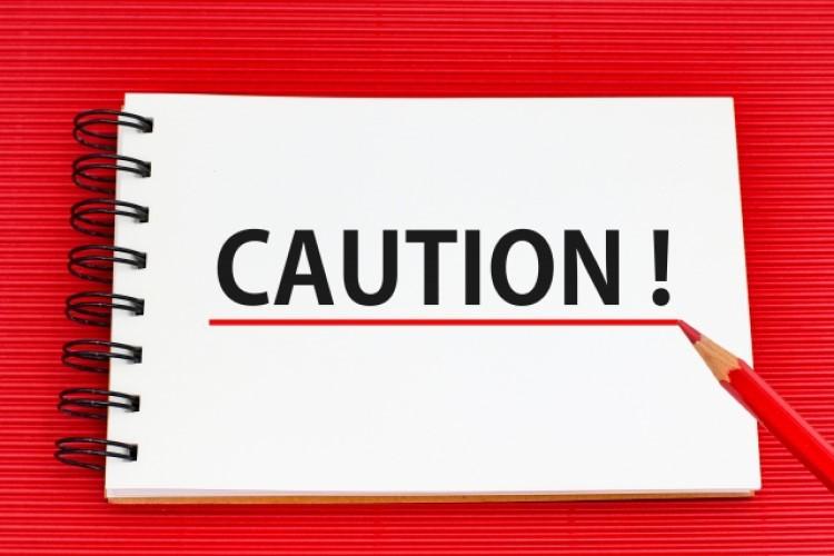 赤い背景の中、スケッチブックに「CAUTION!」と書かれた画像