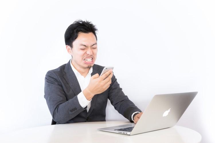 パソコンの前でスマホ片手に顔をしかめる男性の画像