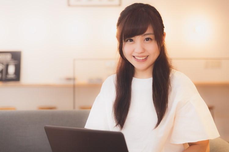 ノートパソコンを前に笑顔で座っている女性の画像