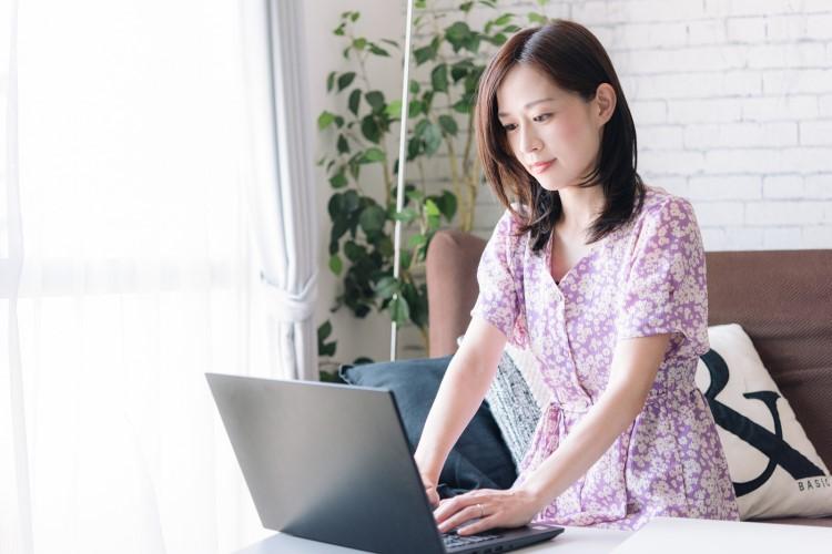 ノートパソコンでタイピングしている女性の画像